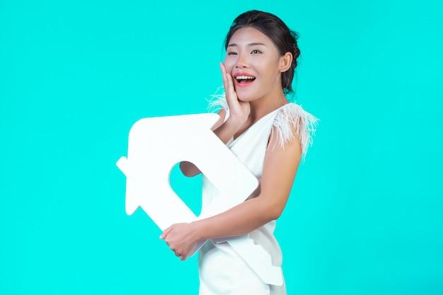 Het meisje droeg een wit shirt met lange mouwen en een bloemmotief, met het huissymbool en verschillende gebaren met een blauw.