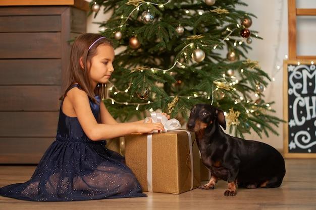 Het meisje droomt voordat ze het kerstcadeautje voor de kerstman opent