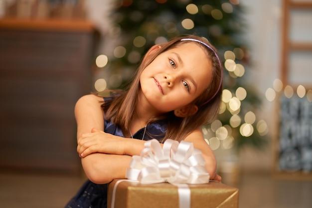 Het meisje droomt voordat ze kerstcadeautjes opent