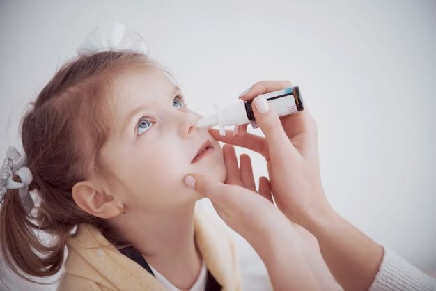 Het meisje druppelt in haar neus met een spray van kou