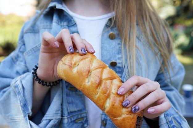 Het meisje eet broodje met chocolade op de straat