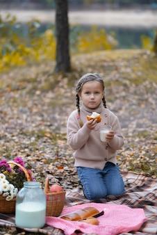Het meisje eet een broodje en drinkt melk in het park