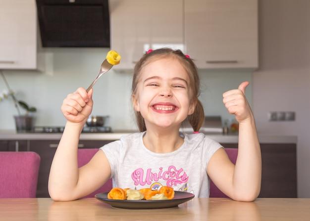 Het meisje eet kleurrijke bollen.