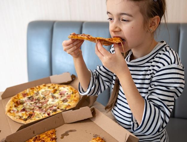 Het meisje eet smakelijke kaaspizza voor de lunch.