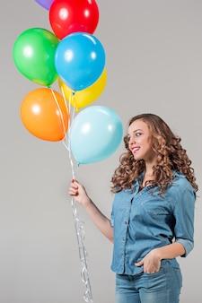 Het meisje en de bos kleurrijke ballonnen op een grijze muur