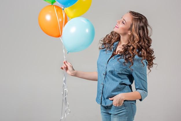 Het meisje en de bos van kleurrijke ballonnen op grijs