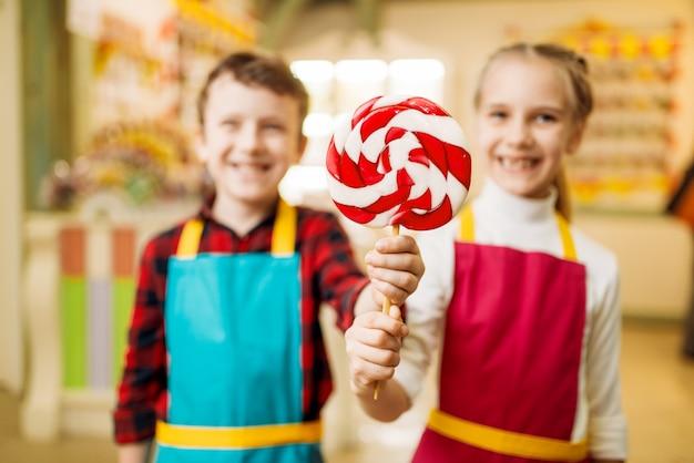 Het meisje en de jongen houden verse lolly in handen. kinderen in werkplaats bij patisserie leren handgemaakte karamel maken. vakantieplezier in de snoepwinkel