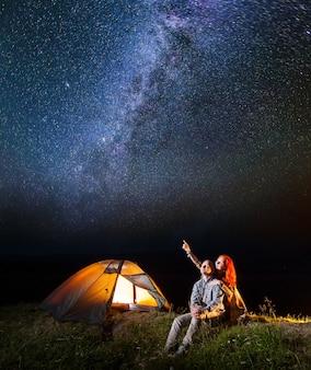 Het meisje en de kerel die bekijken glanst sterrige hemel bij nacht