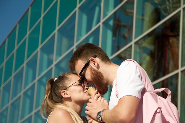 Het meisje en de kerel van de manier in afzetkleren die roomijs eten en bij elkaar in een pretpark glimlachen