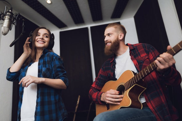 Het meisje en de kerel zingen lied aan gitaar in moderne opnamestudio