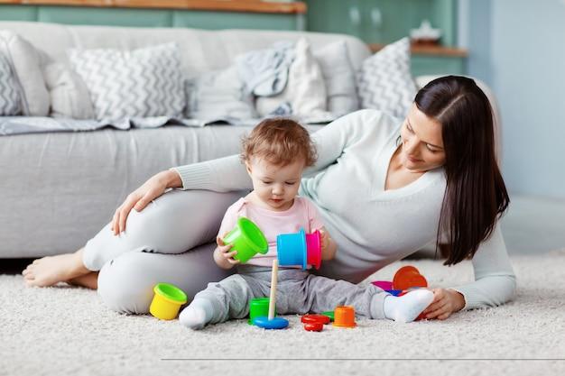 Het meisje en de moeder spelen op de vloer op een licht tapijt met helder speelgoed, bouwen een toren