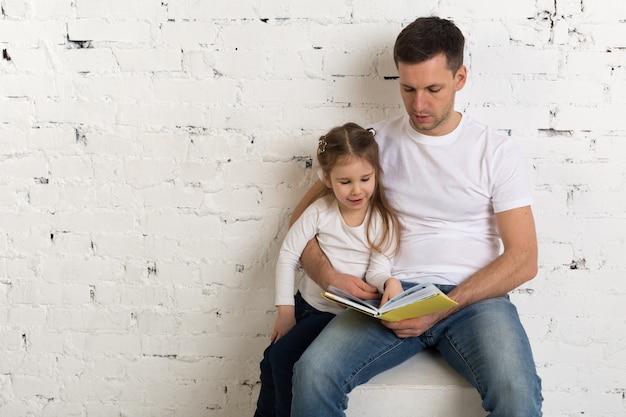 Het meisje en de vader genieten samen van het lezen van boek