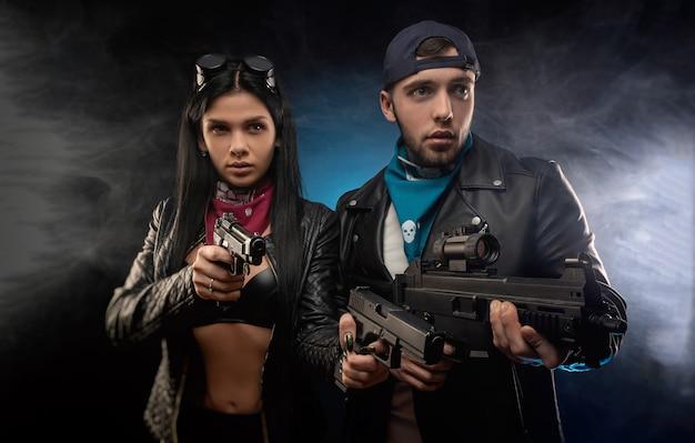 Het meisje en een jongen in een leren jas met een pistool