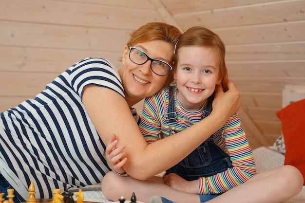 Het meisje en haar moeder glimlachen. portret van een dochter en een moeder