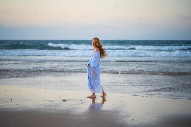 Het meisje ervaart geluk aan de kust. concept: vreugde, geluk, rust