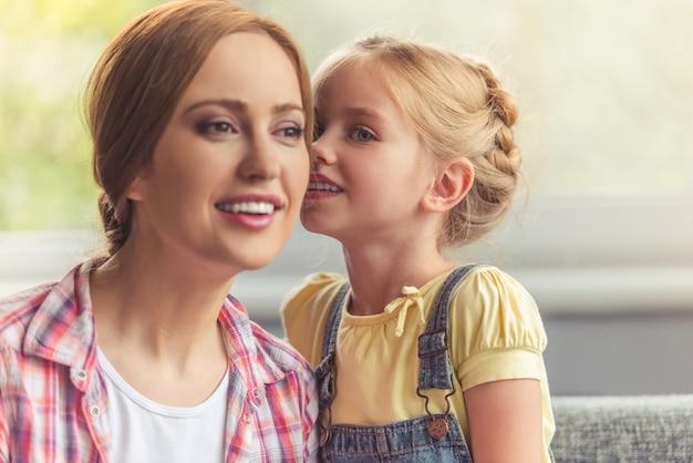 Het meisje fluistert iets in het oor van haar mooie moeder