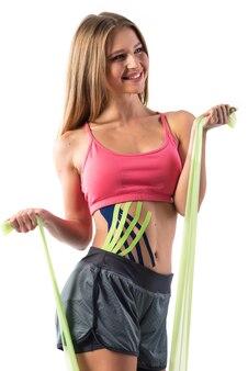 Het meisje gaat sporten, kinesiotapes op haar buik geplakt.