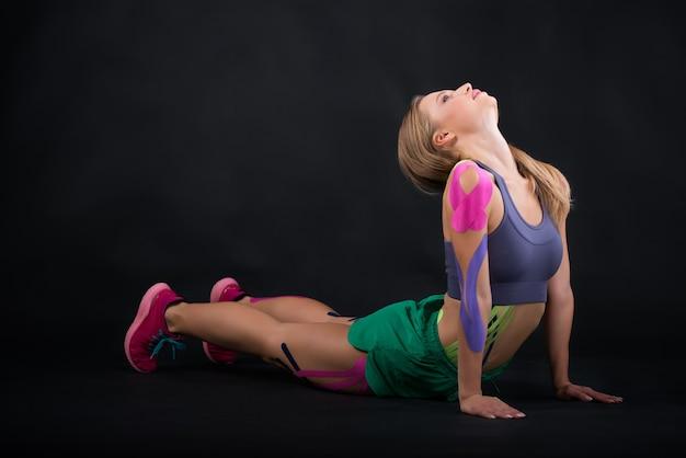 Het meisje gaat sporten, kinesiotapes op haar lichaam geplakt.
