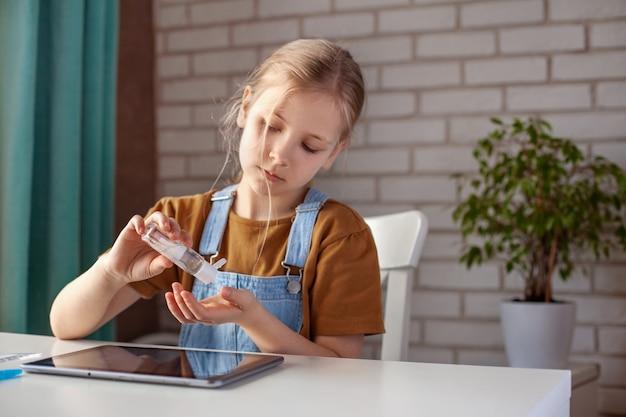 Het meisje gebruikt een antiseptische handgel op alcoholbasis terwijl ze huiswerk maakt met een tablet. preventie, handdesinfectie, infectiepreventie, covid-19-uitbraak