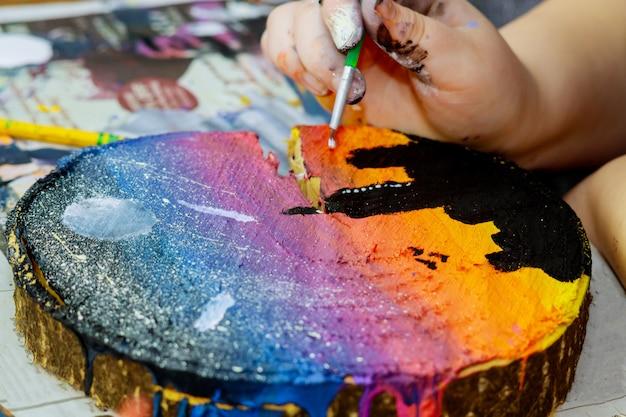 Het meisje gebruikt gekleurde verven borstelt een beeld in houten