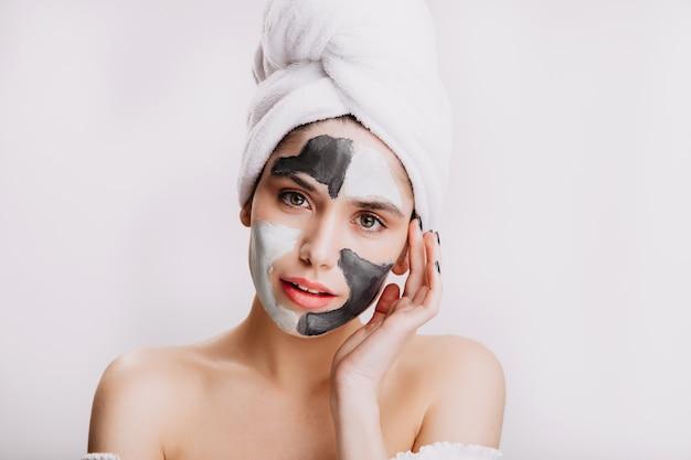 Het meisje gebruikt witte en zwarte klei om de huid te verbeteren en te reinigen. portret van model in handdoek na het wassen van haar haar.