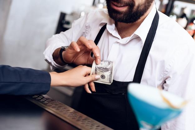 Het meisje geeft de barman de betaling voor de bestelling.