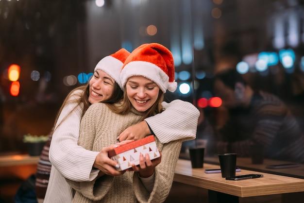 Het meisje geeft een cadeau aan haar vriendin in caffe
