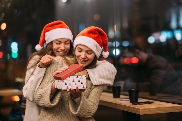 Het meisje geeft een cadeau aan haar vriendin in het café