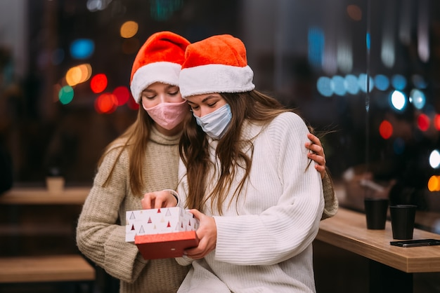 Het meisje geeft een geschenk aan haar vriendin in cafe