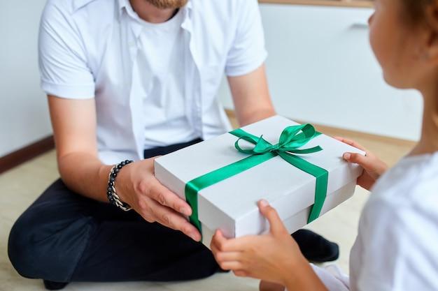 Het meisje geeft haar knappe vader een giftdoos op vaderdag