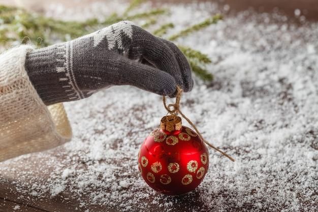 Het meisje geeft rode kerstmisbal