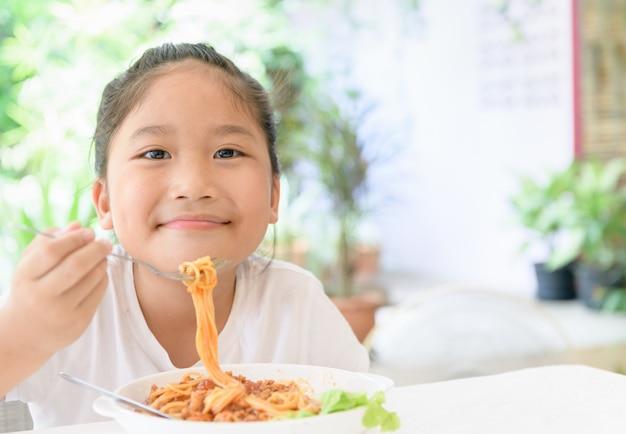 Het meisje geniet van etend spaghetti met varkensvleessaus