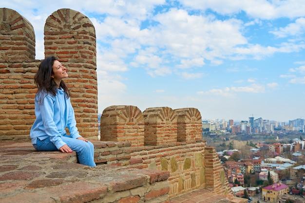 Het meisje geniet van het uitzicht en de stilte terwijl ze op de muur van een oud fort met uitzicht op de stad zit.