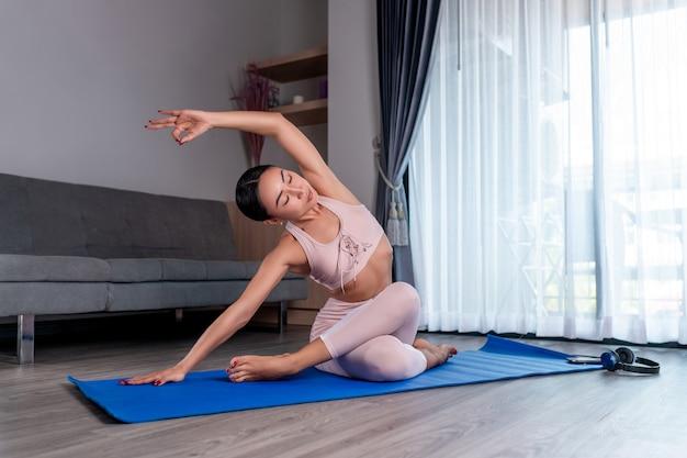 Het meisje geniet van yoga, zittend met gekruiste benen