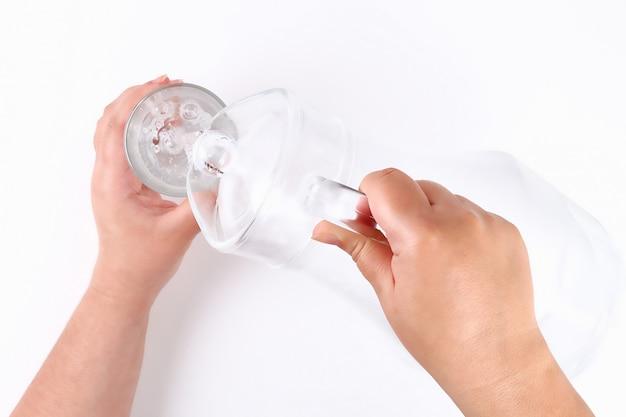 Het meisje giet water uit een kruik in glas