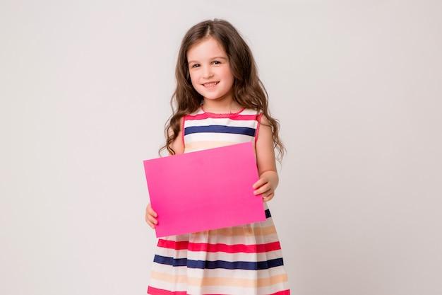 Het meisje glimlacht en houdt een leeg roze document vast