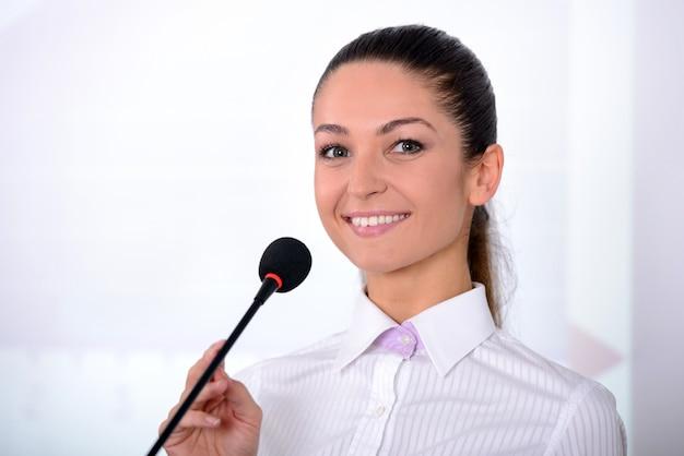 Het meisje glimlacht en stelt bij camera dichtbij microfoon.