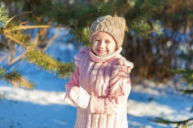 Het meisje glimlacht in de winterbos. gelukkige jeugd. kids outdoors.winter fun holiday concept