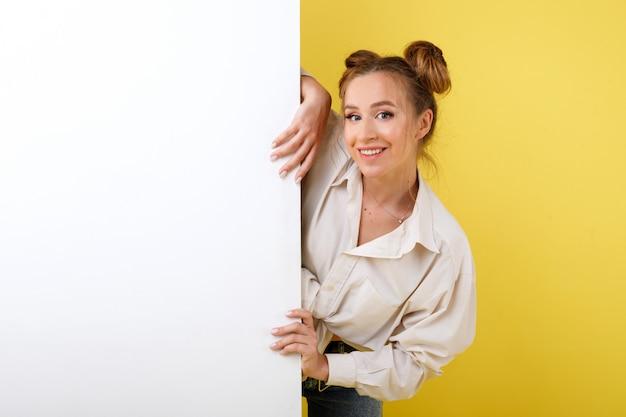 Het meisje glimlacht met witte banner op gele ruimte