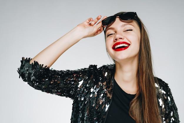Het meisje glimlacht vrolijk, bedekt haar ogen en heft een zwarte bril op met haar hand op haar voorhoofd. lippen rode lippenstift. lichte achtergrond