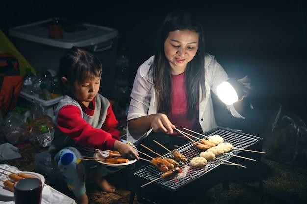 Het meisje grilt vlees en hotdogs voor diner, op de camping met moeder en familie