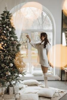 Het meisje hangt een stuk speelgoed aan een kerstboom
