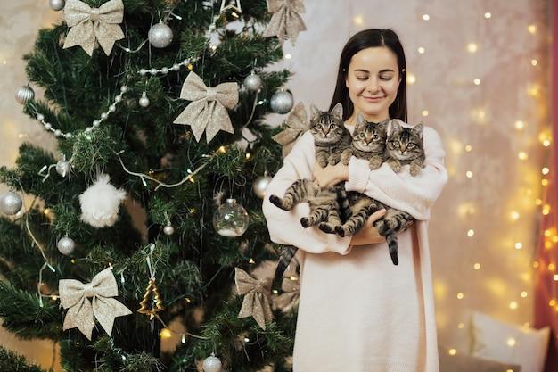 Het meisje heeft drie gestreepte kittens