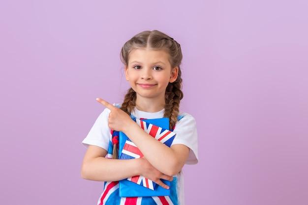 Het meisje heeft een engels leerboek in haar handen en wijst met haar vinger opzij.
