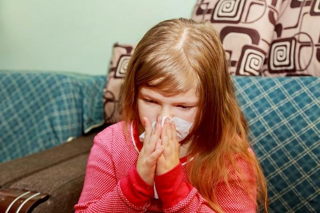 Het meisje heeft een loopneus en blaast haar neus in een papieren zakdoek