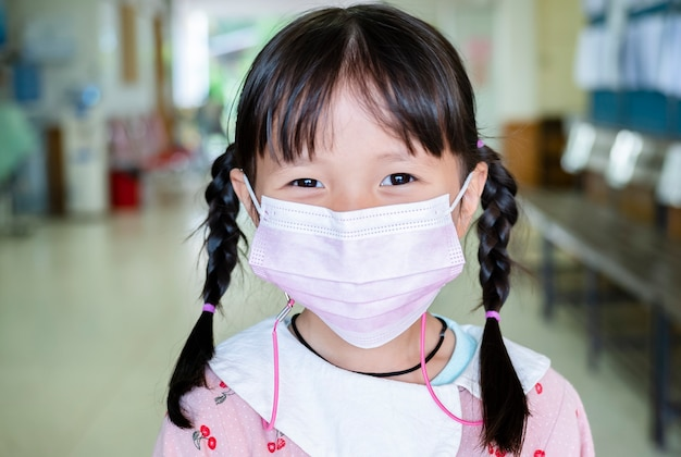 Het meisje heeft een stoffen masker om zichzelf te beschermen tegen het coronavirus, een nieuwe normale levensstijl na de covid-19-uitbraak
