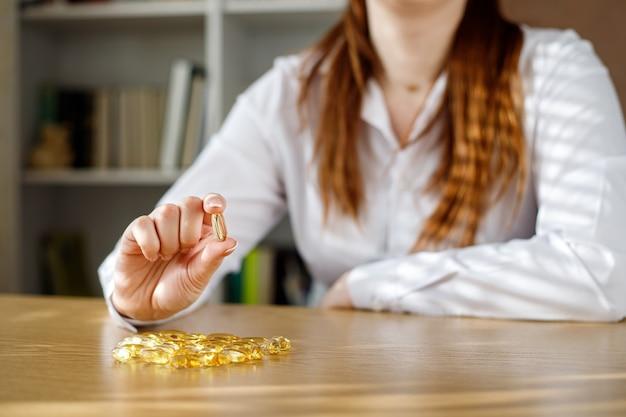 Het meisje heeft een visoliecapsule in haar hand. omega-3 capsules op tafel en in de hand van de dokter.