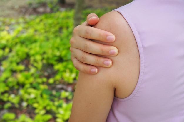 Het meisje heeft pijn in de schouderspieren.