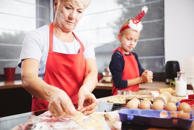 Het meisje helpt haar grootmoeder om koekjes te maken