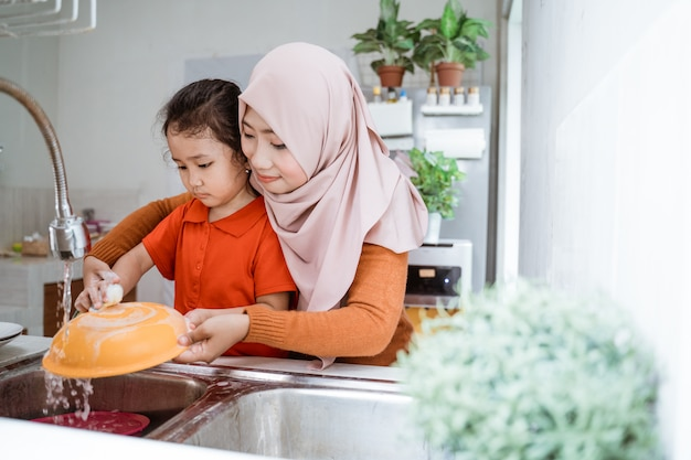 Het meisje helpt haar moeder bij het afwassen